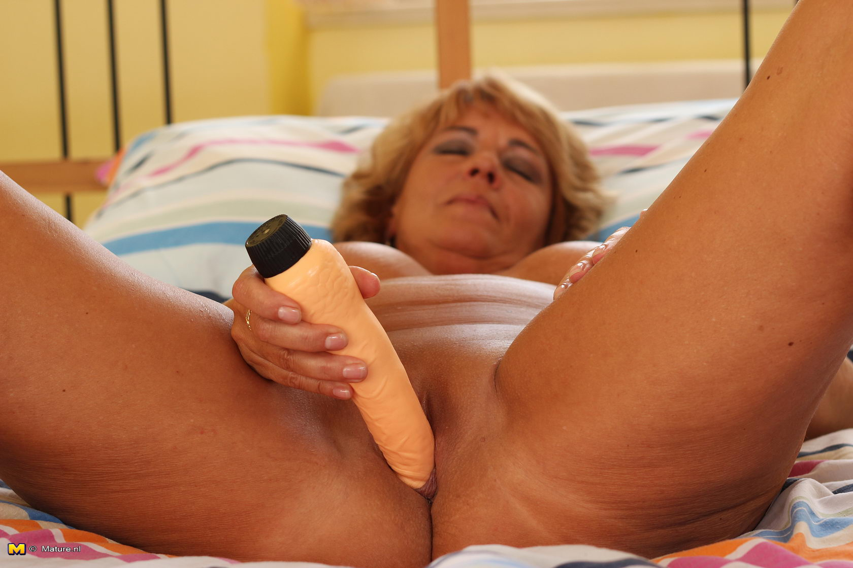 Blonde mature slut masturbating on her bed